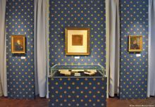 In der Mitte die Brüder Grimm über den Handexemplaren ihrer Kinder- und Hausmärchen, links und rechts Märchenbeiträger